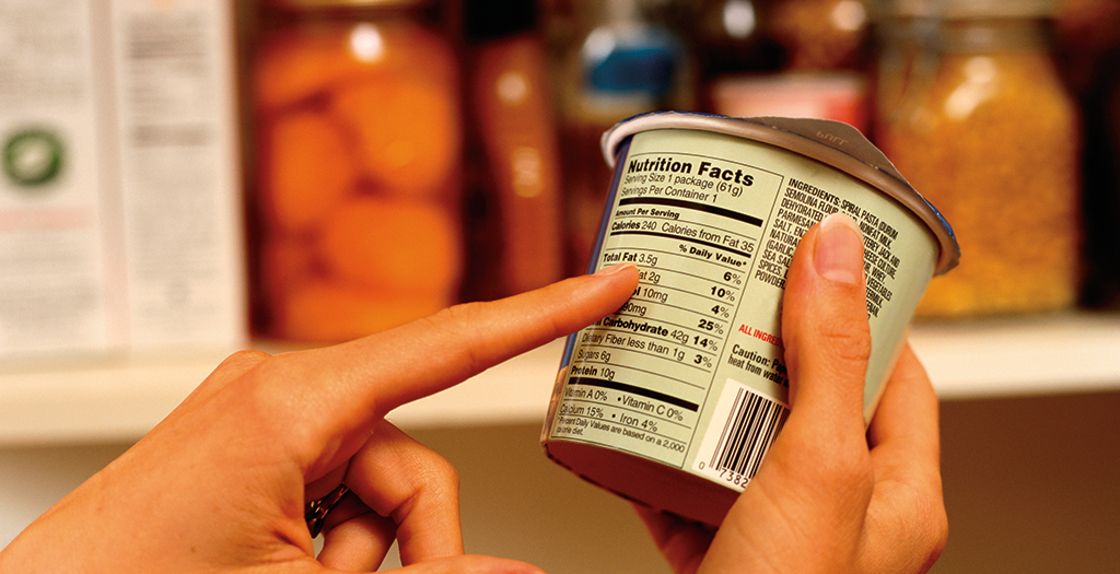 Hands Holding And Pointing To A Container's Food Label