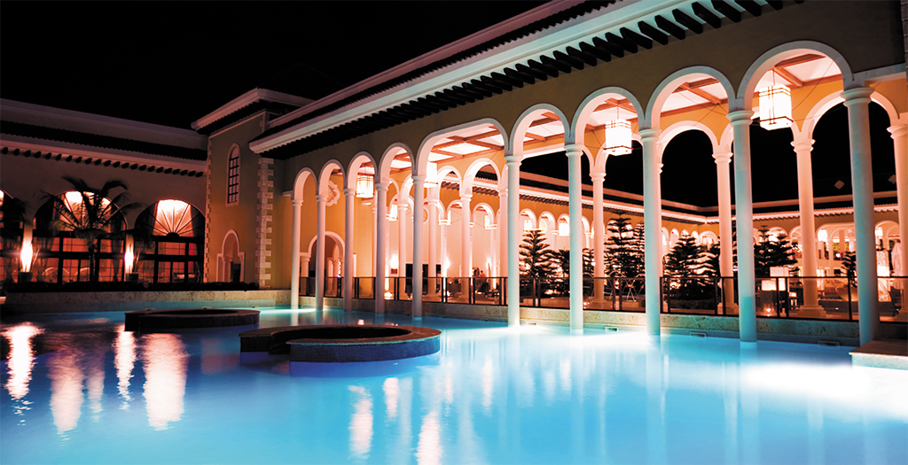 A Pool At Night Next To A Fancy And Bright Building