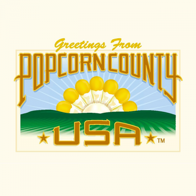 """""""Greetings From Popcorn County"""" Logo With A Drawing Of The Countryside And A Popcorn Kernel Sun"""