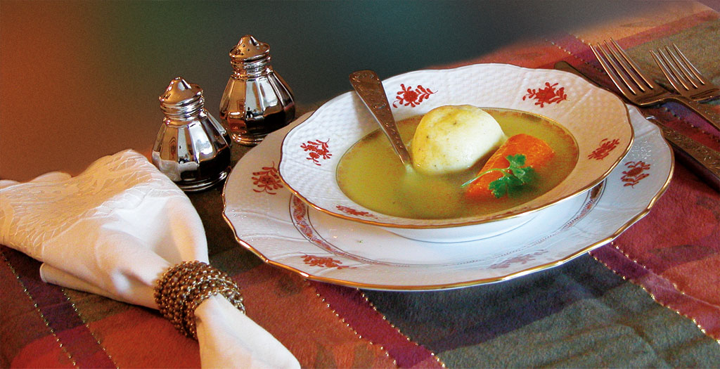 Soup In A Decorated Bowl On A Table With Salt And Pepper Shakers, 2 Forks, And A Cloth Napkin