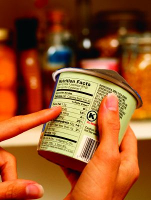 Someone Looking at the FDA Nutritional Label on a Food Product in a Store
