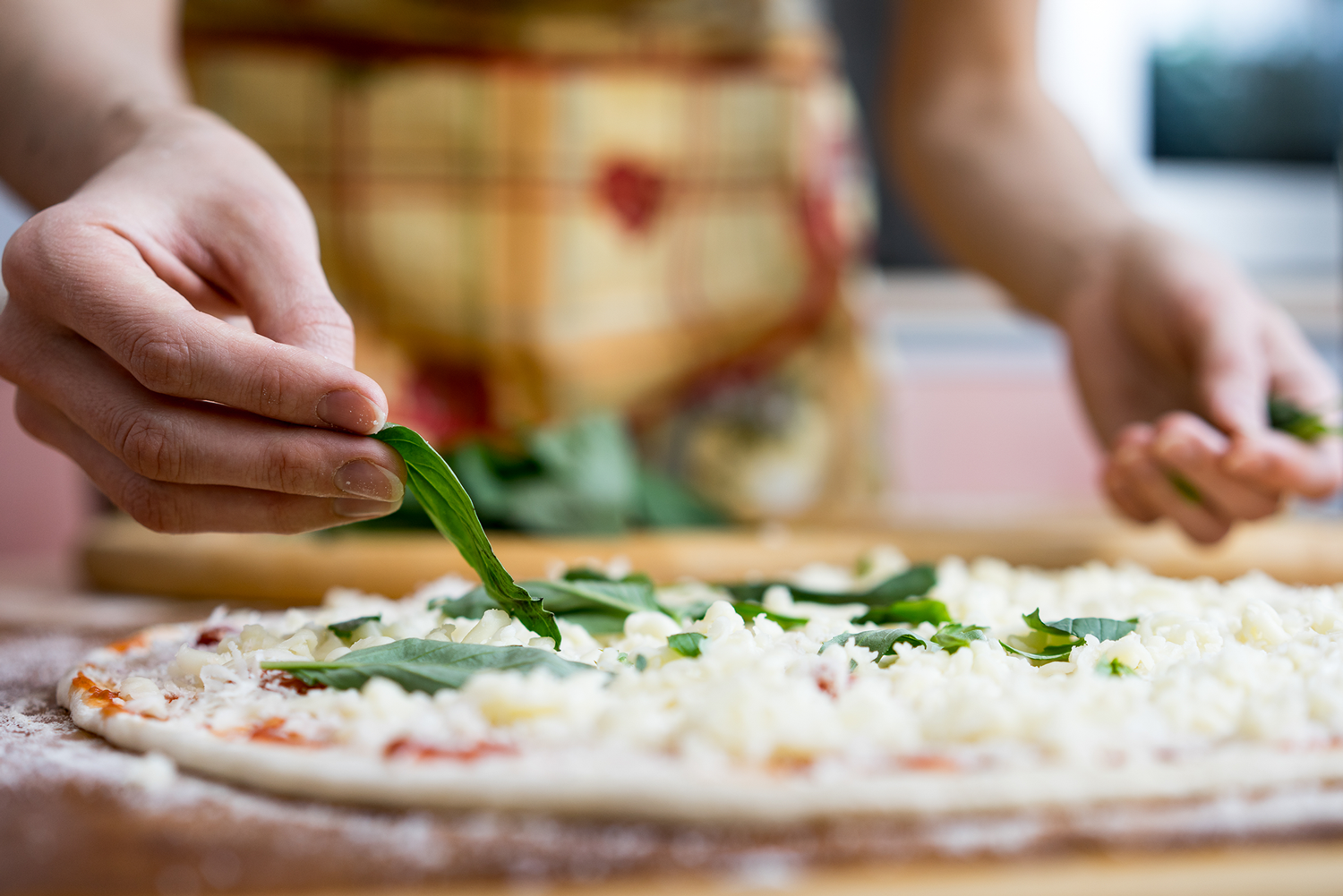 Someone Adding Basil Leaves to an Uncooked Kosher Pizza